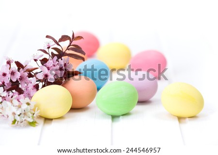 Pastel colored Easter eggs next to blooming branch - stock photo