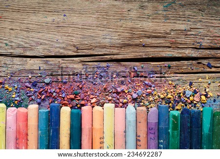 Pastel crayons and pigment dust on old wooden background. - stock photo