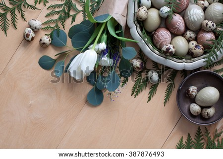 Pastel Easter eggs dyed with natural dyes with bouquet of flowers on wooden planks - stock photo