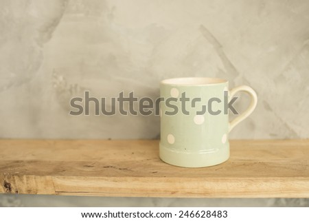 Pastel Green cup with dot on wooden background and cement wall. - stock photo