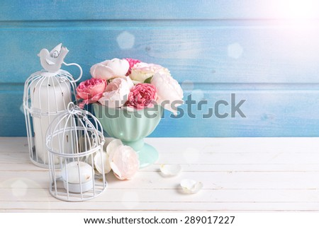 Pastel roses in turquoise vase and candles in ray of light on white wooden  background against blue wall. Place for text. Selective focus. - stock photo