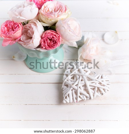 Pastel roses in turquoise vase and decorative heart on white wooden  background. Selective focus. Square image. - stock photo