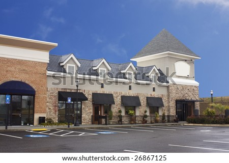 pastel stucco and brick upscale commercial strip mall - stock photo