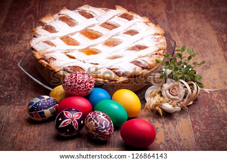 PASTIERA and colorful Easter eggs. Pastiera is a traditional Italian Easter pie made with wheat and ricotta cheese; at Naples is also known as Pizza Gran. - stock photo