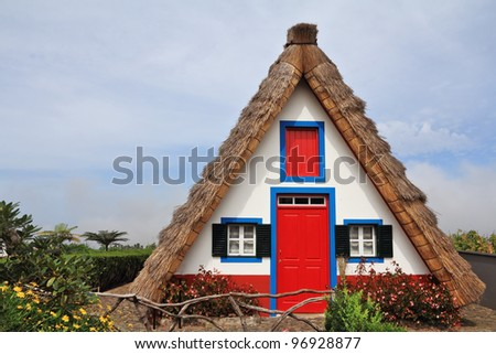 Pastoral landscape. Small rural house with a triangular thatched roof. The red door and small windows with shutters. Madeira, the city of Santana - stock photo