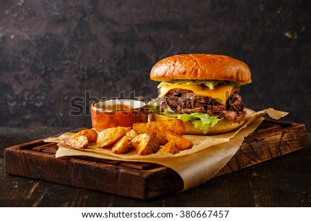 Pastrami Burger Takeaway snack with sliced Roast beef and potato wedges on dark background - stock photo