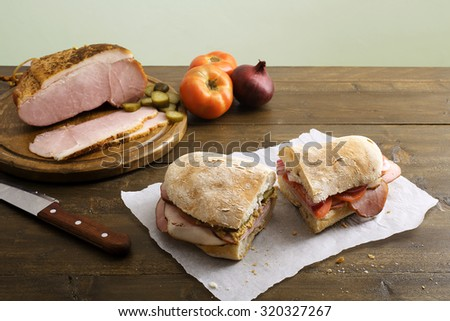 Pastrami sandwich on rustic table - stock photo