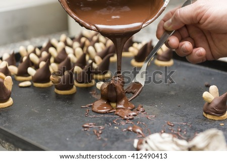 pastry chef covering the biscuits with melted chocolate - stock photo