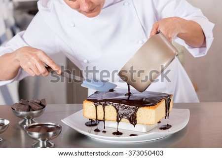 Pastry chef in the kitchen decorating a cake of chocolate - stock photo