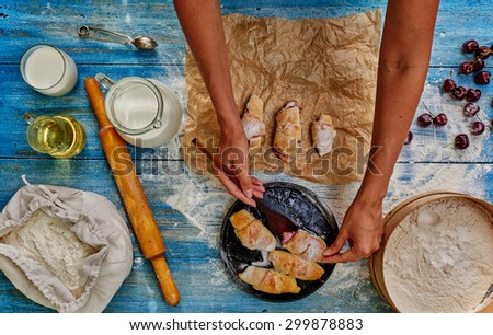 Pastry chef puts bagels on paper from the cast-iron cookware in which they bake, standing next to the milk - stock photo