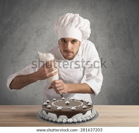 Pastry cook prepares a chocolate and cream cake - stock photo