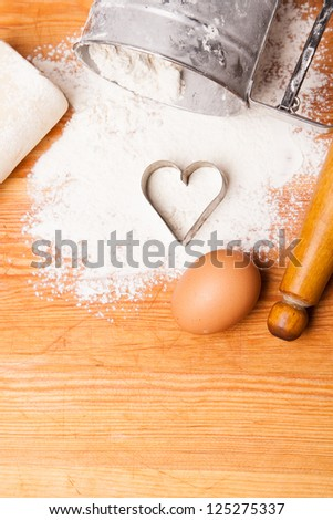 pastry, rolling pin, eggs and figures for cookies on wooden - stock photo