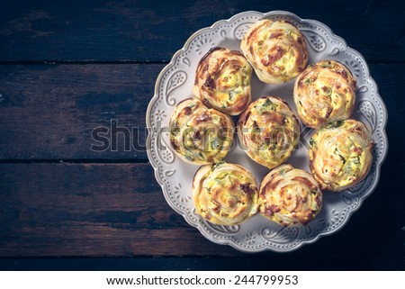 Pastry snack stuffed with ham and cheese on wooden background with blank space - stock photo