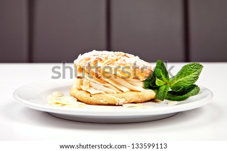 Pastry with sugar powder, almonds and mint on white background - stock photo