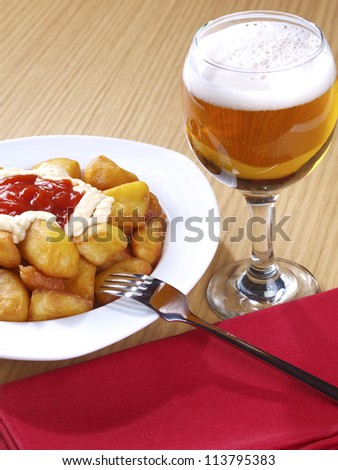 Patatas Bravas � Hot spicy fried potatoes �Patatas Bravas�,  Fried potatoes served with mayonnaise and a hot spicy sauce. Spanish Tapa. �Tapas� are typical spanish appetizer. - stock photo