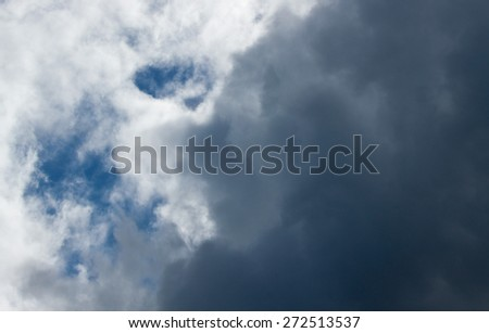 patch of blue sky showing through grey clouds  - stock photo