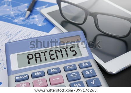 PATENTS Calculator  on table with Office Supplies. ipad - stock photo