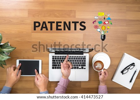 PATENTS Two Businessman working at office desk and using a digital touch screen tablet and use computer objects on the right, top view copy space - stock photo