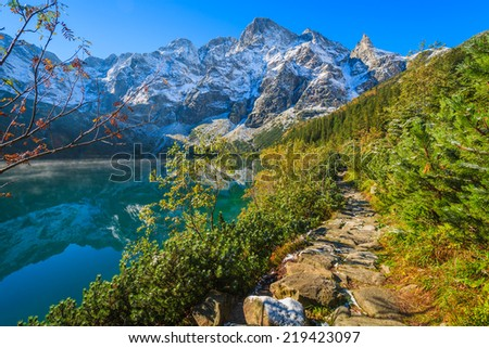 Path along Morskie Oko lake in autumn colours with fresh snow covered peaks, High Tatra Mountains, Poland - stock photo