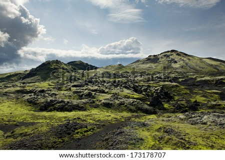 Path among rocks covered with moss at Lakagigar area on a sunny day, Iceland - stock photo