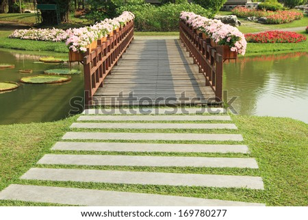 Path and pedestrian bridge decorated with flower pot - stock photo