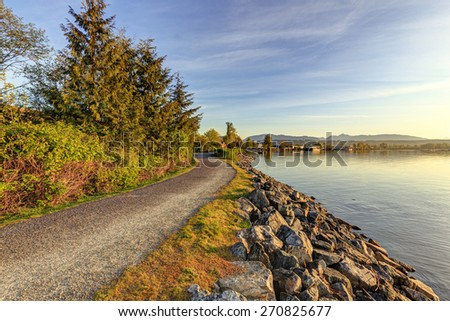 Path in a park by a river at sunrise - stock photo