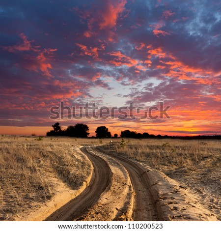 path on sandy steppe on sunset - stock photo
