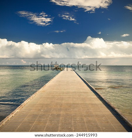 Path on the pier by the ocean with blue sky and clouds in the background on a beautiful summer day. Taken in the tropical paradise of Key West Florida, USA. Desaturated instagram processing - stock photo