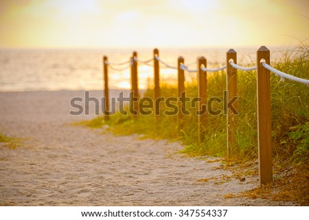 Path on the sand going to the ocean in Miami Beach Florida at sunrise or sunset, beautiful nature landscape, retro instagram filter and shallow  focus for vintage looks - stock photo