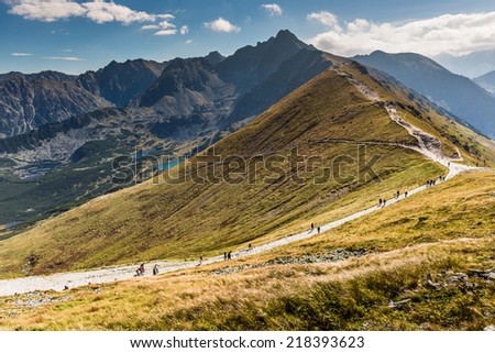 Path on the steep side of Kasprowy Wierch in Tatra mountains and a view of the border between Poland and Slovakia. - stock photo