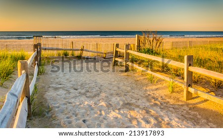 Path over sand dunes to the Atlantic Ocean at sunrise in Ventnor City, New Jersey. - stock photo