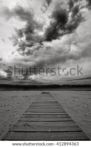 path to the beach on a cloudy day, wooden boardwalk across a sandy beach, footpath at the beach - stock photo
