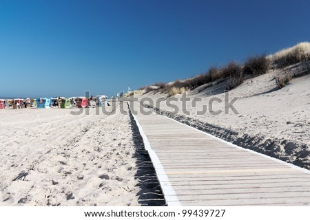 Path to the beach on Langeoog with beach chairs and the North Sea in the background - stock photo
