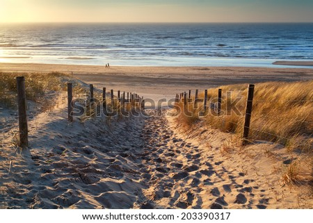 path to the sea and couple on beach at sunset, North sea, Holland - stock photo