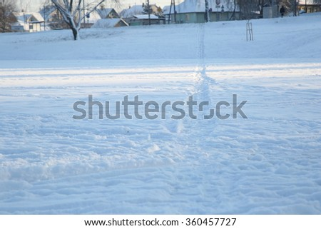 Paths  in snow on surface of frozen lake leading to distant shore on sunny winter day. - stock photo