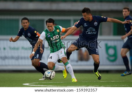 PATHUMTHANI,THAILAND-20 JULY:Teeratep Winothai #14 (green)of Bangkok Glass fc. in action during Thai Premier League between Bangkok Glass fc.and Burirum Utd.at Leo Stadium on July 20,2013 in Thailand - stock photo