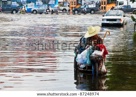 PATHUMTHANI, THAILAND - OCTOBER 18 -Thai flood hits Central of Thailand, cripple man sitting on bicycle navigating through the flood- Tuesday october 18, 2011 in Pathumthani, Thailand - stock photo