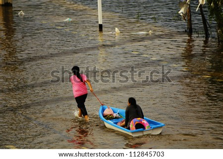 PATHUMTHANI, THAILAND - OCTOBER 16 : Unidentified people travel by boat due to the worst flood in Thailand for more than 50 years on October 16, 2011 in Pathumthani, Thailand. - stock photo
