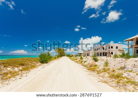 Pathway along a beautiful Bahamas seaside on the left and abandoned houses on the right - stock photo