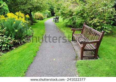 Pathway and Wooden Bench in a Beautiful Leafy Landscape Garden - stock photo