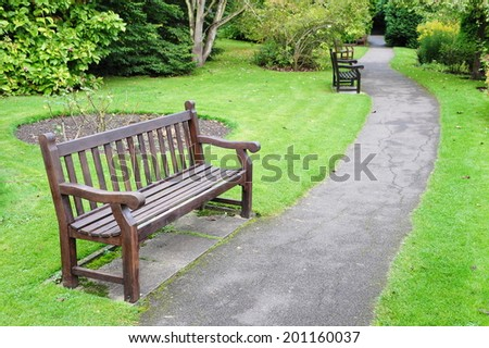 Pathway and Wooden Bench in a Beautiful Park - stock photo