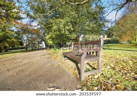 Pathway bench in a Beautiful Public Park, London, UK - stock photo