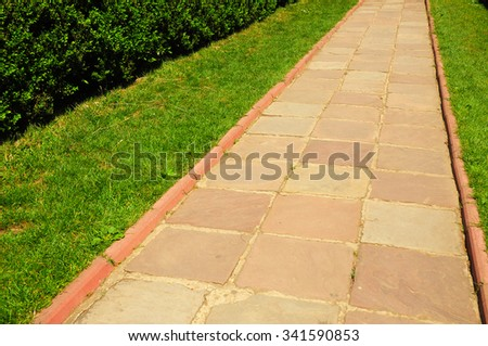 Pathway in Garden with concrete bumps. Colorful brick footpath. - stock photo