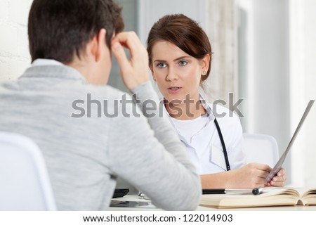 Patient and doctor discussing x-ray results - stock photo