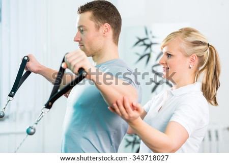 Patient at the physiotherapy doing physical exercises with Bowden cable  - stock photo