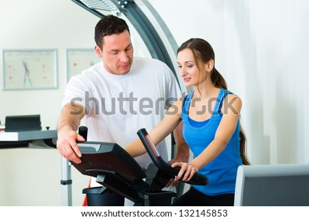Patient at the physiotherapy making physical exercises with her therapist - stock photo