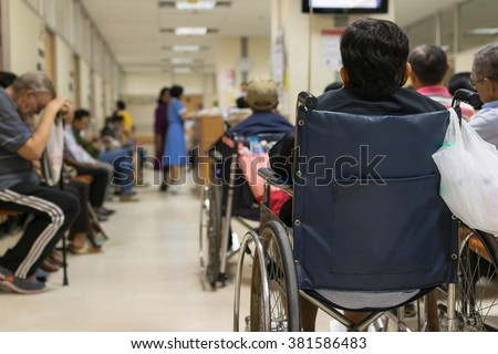 Patient elderly on wheelchair and many patient waiting a doctor and nurse in hospital - stock photo
