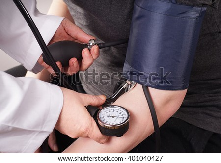 Patient gets Blood pressure check up by the Doctor - stock photo