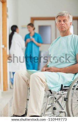 Patient in a wheelchair looking at camera in hospital corridor - stock photo