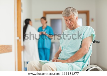 Patient in a wheelchair looking down in hospital ward - stock photo